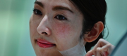 An employee for Japanese cosmetics company Kao removes a super thin transparent layer after using a palm-sized diffuser on her face, during a product demonstration in Tokyo. (Photo: © Charly Triballeau / AFP)