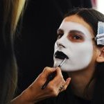 Black lipstick against white face paint backstage at Aalto