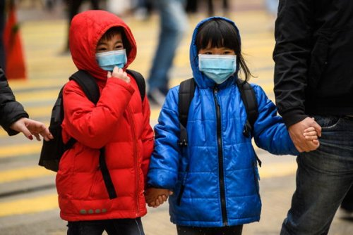Children wearing face masks cross the road during a public holiday for the...